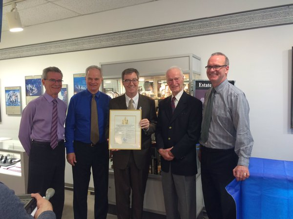 Mayor Jim Watson presenting a plaque congratulating Richard, Cameron, Douglas and Geoffrey for 100 Years of business in Ottawa.